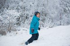 Śliczna chłopiec chodzi w śniegu w parku w zimie Obrazy Stock