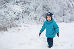Śliczna chłopiec chodzi w śniegu w zima parku Obrazy Royalty Free