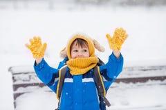 Śliczna chłopiec, chwytający płatki śniegu w parku na zima dniu Zdjęcie Royalty Free