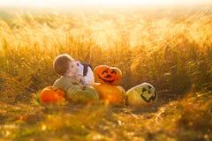 Śliczna chłopiec cieszy się jesień czas Chłopiec z baniami dla Halloween nad zmierzchu lub wschodu słońca tłem Obraz Royalty Free