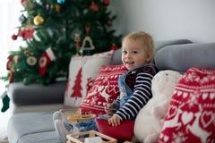 Śliczna chłopiec, czyta książkę przed choinką w domu zdjęcie royalty free