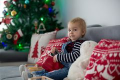 Śliczna chłopiec, czyta książkę przed choinką w domu obraz stock