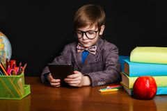 Śliczna chłopiec czyta obsiadanie i ebook przy szkolnym biurkiem tylna szkoły Zdjęcia Stock