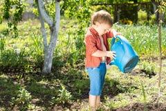 Śliczna chłopiec dolewania woda na jego ciekach Zdjęcia Royalty Free