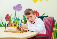Śliczna chłopiec, dzieciak w wózku inwalidzkim rozwiązuje logiczną łamigłówkę w centrum rehabilitacji dla dzieci z specjalnymi po Obraz Royalty Free