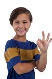 Śliczna chłopiec gestykuluje zadowalającego ręka znaka Zdjęcia Stock
