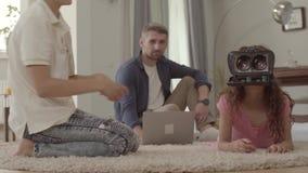 Śliczna chłopiec i dziewczyna kłaść na podłodze na puszystych dywanowych używa rzeczywistość wirtualna szkłach, ojca obsiadanie n zbiory