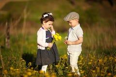 Śliczna chłopiec i dziewczyna na lata polu Obraz Stock