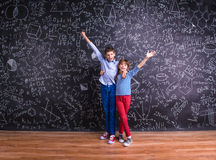 Śliczna chłopiec i dziewczyna przed dużym blackboard Obraz Stock