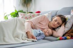 Śliczna chłopiec i jego matka kłama na leżance w żywym pokoju, fotografia stock