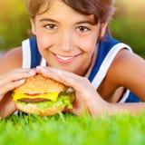 Śliczna chłopiec je hamburger Fotografia Royalty Free
