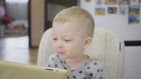 Śliczna chłopiec, je owsiankę dla śniadania w domu, podczas gdy oglądający kreskówkę na pastylce Dzieci i technologia lub zdjęcie wideo