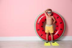 Śliczna chłopiec jest ubranym flippers z nadmuchiwanym pierścionkiem obraz royalty free