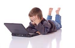 Śliczna chłopiec z laptopem Obrazy Royalty Free