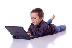 Śliczna chłopiec z laptopem fotografia royalty free