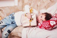 Śliczna chłopiec kłama na kanapie z prezentem w jego rękach Facet z eleganckim Iroquois ostrzyżeniem w modny nowożytnym i odziewa Obrazy Royalty Free