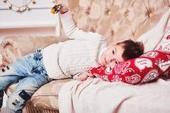 Śliczna chłopiec kłama na kanapie z prezentem w jego rękach Facet z eleganckim Iroquois ostrzyżeniem w modny nowożytnym i odziewa Obraz Stock