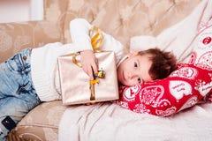 Śliczna chłopiec kłama na kanapie z prezentem w jego rękach Facet z eleganckim Iroquois ostrzyżeniem w modny nowożytnym i odziewa Obrazy Stock