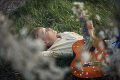 Śliczna chłopiec kłama na trawie z gitarą na zmierzchu Fotografia Stock