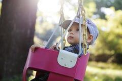 Śliczna chłopiec ma zabawę na huśtawce plenerowej w parku na zmierzchu Obrazy Royalty Free
