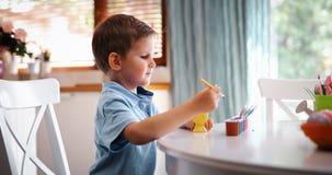 Śliczna chłopiec maluje Easter jajka obrazy stock