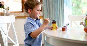Śliczna chłopiec maluje Easter jajka obraz stock