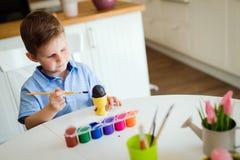 Śliczna chłopiec maluje Easter jajka zdjęcia stock