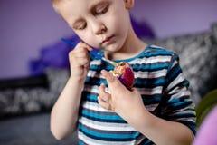 Śliczna chłopiec maluje Wielkanocnego jajko Obrazy Royalty Free