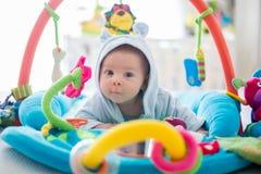 Śliczna chłopiec na kolorowym gym, bawić się z obwieszeniem bawi się w domu Zdjęcie Stock