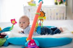 Śliczna chłopiec na kolorowym gym, bawić się z obwieszeniem bawi się w domu Zdjęcie Royalty Free