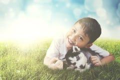 Śliczna chłopiec obejmuje łuskowatego szczeniaka outdoors Zdjęcia Royalty Free