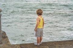 Śliczna chłopiec ogląda ocean fala stoi na brzeg obraz stock