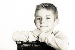 Śliczna chłopiec Opiera na krześle w Monochromatycznym kolorze Zdjęcia Royalty Free
