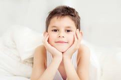 Śliczna chłopiec pod koc w łóżku w sypialni do okłamywania T obrazy stock