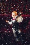 Śliczna chłopiec pokazuje dużego zegar z czasem przed nowy rok nocą zdjęcie stock