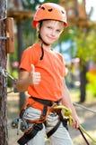 Śliczna chłopiec pokazuje kciuk up z wspinaczkowym wyposażeniem wewnątrz Obraz Royalty Free