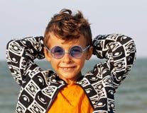 Śliczna chłopiec przy seacoast w mod clothers i błękitnych szkłach Obrazy Royalty Free