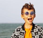 Śliczna chłopiec przy seacoast w mod clothers i błękitnych szkłach Fotografia Royalty Free