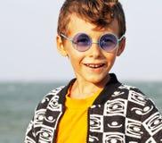 Śliczna chłopiec przy seacoast w mod clothers i błękitnych szkłach Obrazy Stock