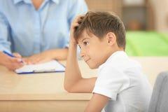 Śliczna chłopiec przy stołem w psychologach biurowych Obraz Stock