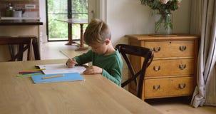 Śliczna chłopiec robi pracie domowej przy łomotać stół w wygodnym domu 4k zbiory wideo