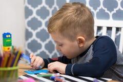Śliczna chłopiec robi preschool malować i pracie domowej fotografia stock