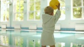 Śliczna chłopiec rzuca żółtą piłkę basen przy czasu wolnego centrum dopłynięcie basenu dopłynięcie Chłopiec jest ubranym małego b zbiory wideo