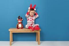Śliczna chłopiec siedzi na ławce w Bożenarodzeniowych piżamach zdjęcie stock