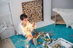 Śliczna chłopiec siedzi na podłoga i trzyma bożonarodzeniowe światła Obraz Stock