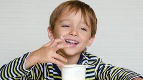 Śliczna chłopiec siedzi przy stołem i je jogurt, doświadcza emocje: radość, szczęście i zabawa, Dziecko zbiory