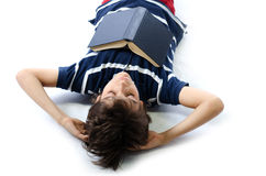 Śliczna chłopiec spadał uśpiony podczas gdy studiujący szkolną książkę obraz stock