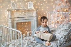 Śliczna chłopiec trzyma Bożenarodzeniowego prezent Obrazy Royalty Free