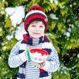 Śliczna chłopiec trzyma dużą filiżankę, gorącej czekolady marshmallo i napój i Obrazy Royalty Free