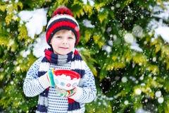 Śliczna chłopiec trzyma dużą filiżankę, gorącej czekolady marshmallo i napój i Fotografia Royalty Free